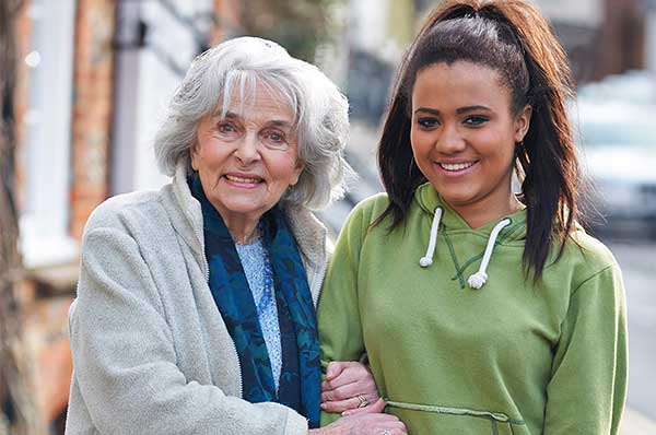 Aged home care services - girl helping older woman walk